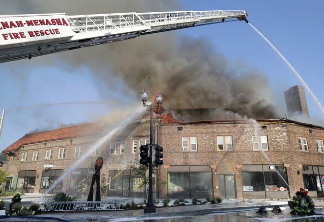 Firefighters work to extinguish an Aug. 10 fire that ravaged the Brin Building in downtown Menasha.