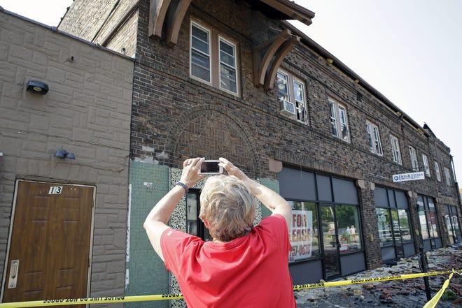 Kathy Humski, of the Menasha Historical Society, records the Brin Building on Saturday in Menasha.. The structure burned Friday.