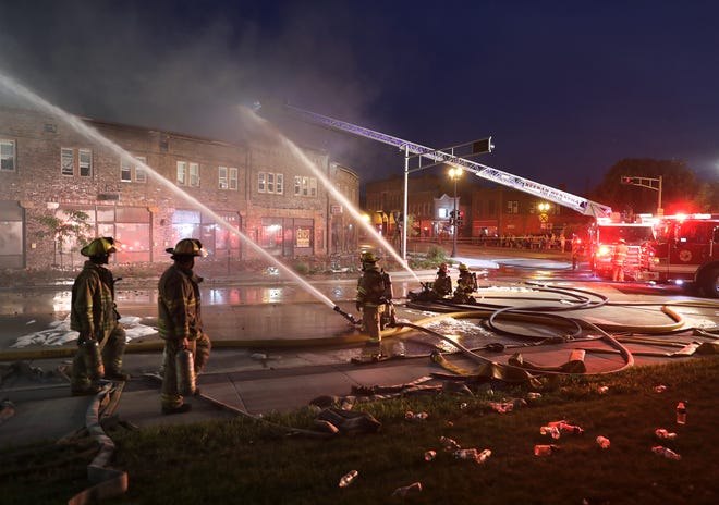 Firefighters from multiple fire departments battle a fire Friday night in the Brin Building in downtown Menasha.  Wm. Glasheen/USA TODAY NETWORK-Wisconsin