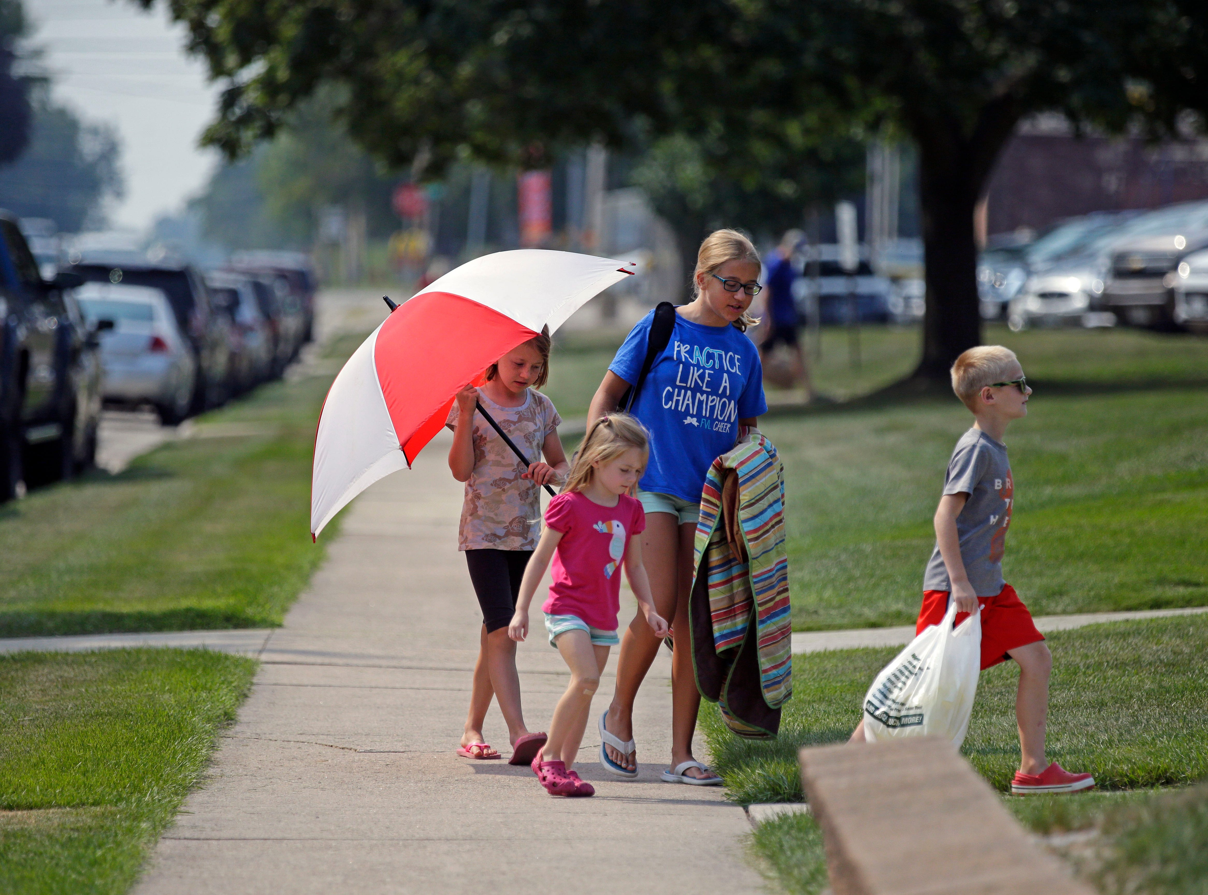 Rachel Raschka, left, Cecelia Frey, Natalie Raschka and Micah Frey make their way to the Hamburger Parade during the 30th annual Burger Fest Saturday, August 11, 2018, in Seymour, Wis.