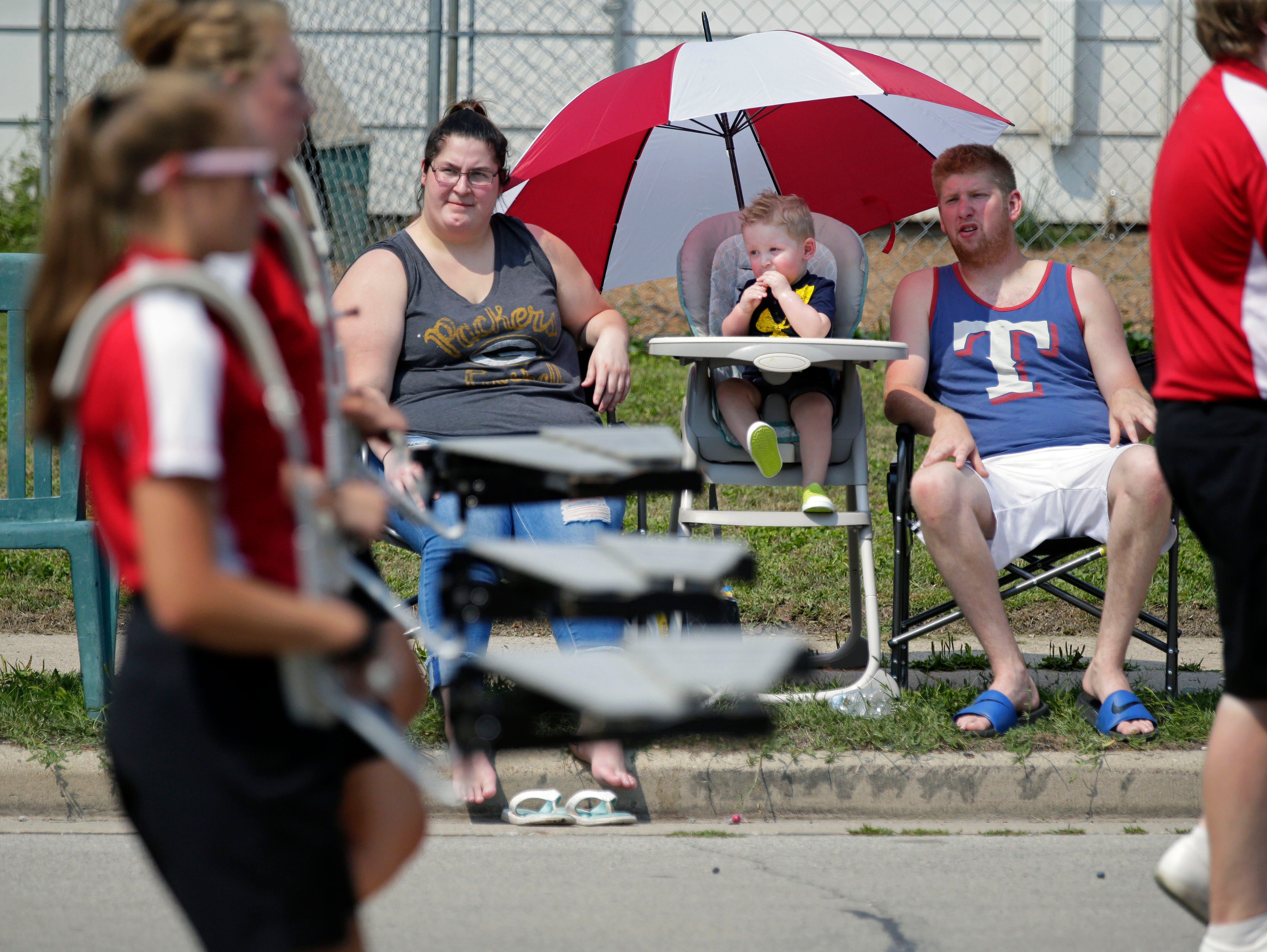 Harrison Miramontes has the best seat in his high chair with an umbrella as he and his parents Vanessa and Harley watch the Hamburger Parade during the 30th annual Burger Fest Saturday, August 11, 2018, in Seymour, Wis.