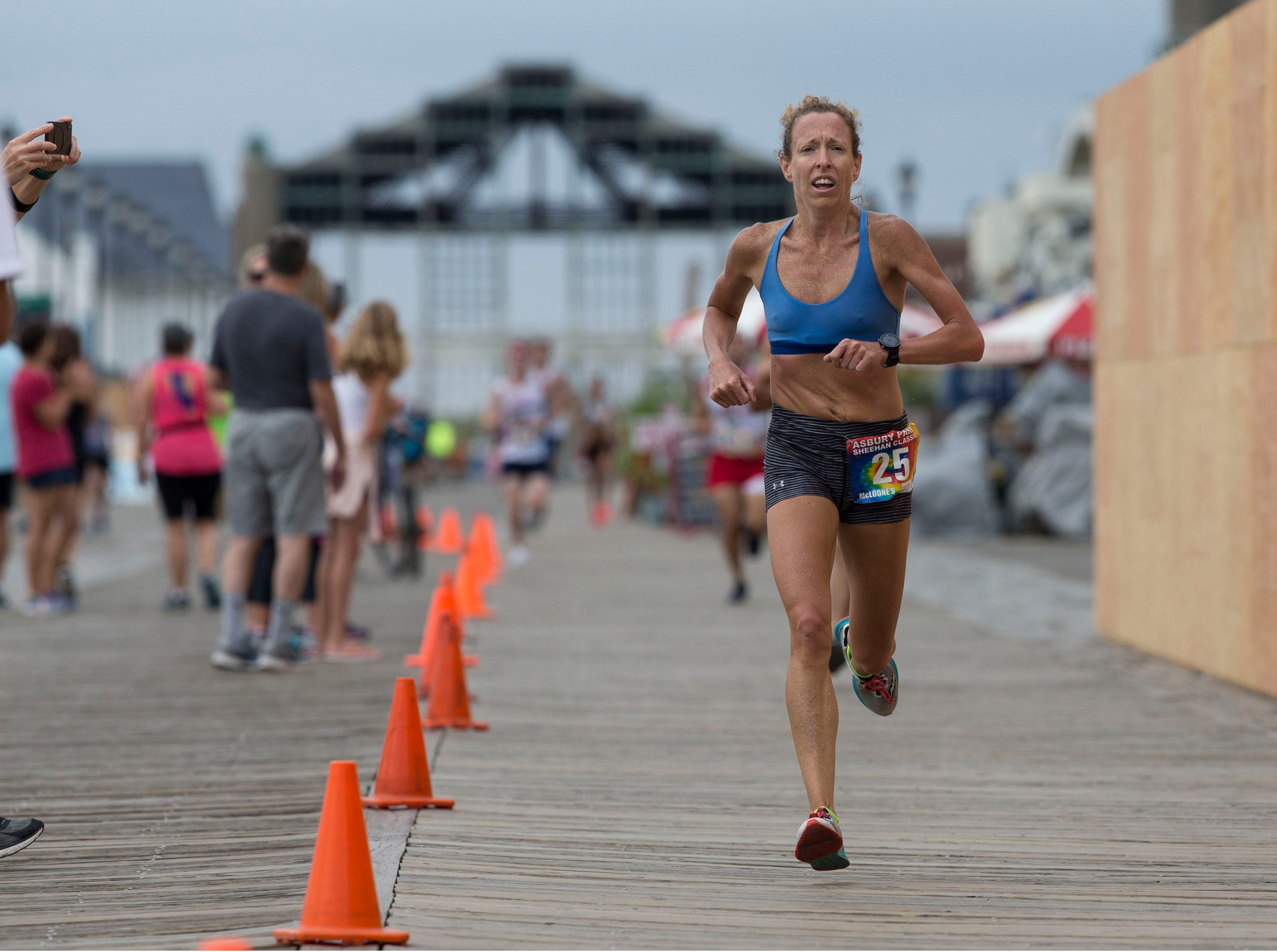 The Asbury Park 5K race makes its way along city streets and finishes after a stretch on the boardwalk. First place female is Roberta Groner of Ledgewood. 