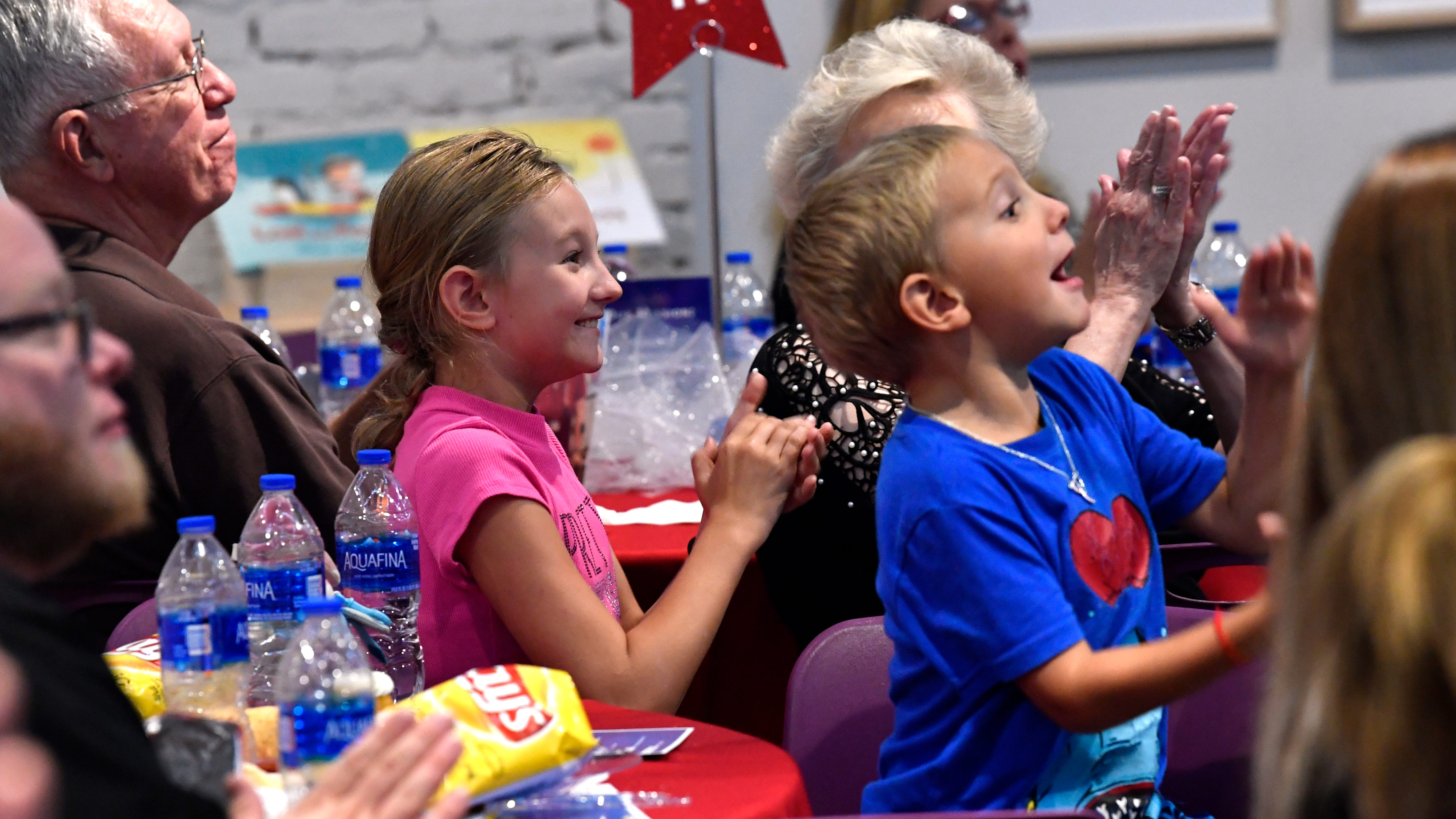 Katy Newman, 9; and her 6-year-old brother Matthew cheer their mother Cynthia Newman during Goodwill's got Talent, a talent show featuring workers from local Goodwill stores, August 9, 2018 at the National Center for Children's Illustrated Literature.