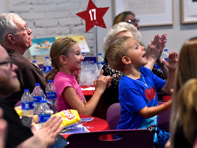 Katy Newman, 9, and her 6-year-old brother Matthew cheer their mother Cynthia Newman during Goodwill's Got Talent, a talent show featuring workers from local Goodwill stores, on Thursday at the National Center for Children's Illustrated Literature.