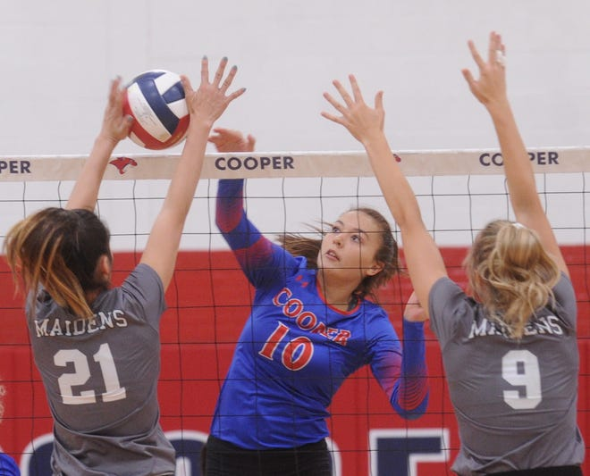 Cooper's Brianna Garcia (10) hits the ball while two Seminole players defend. Cooper beat the Maidens 25-22, 25-13 during pool play at the Bev Ball Classic on Friday, Aug. 10, 2018 at Cougar Gym.