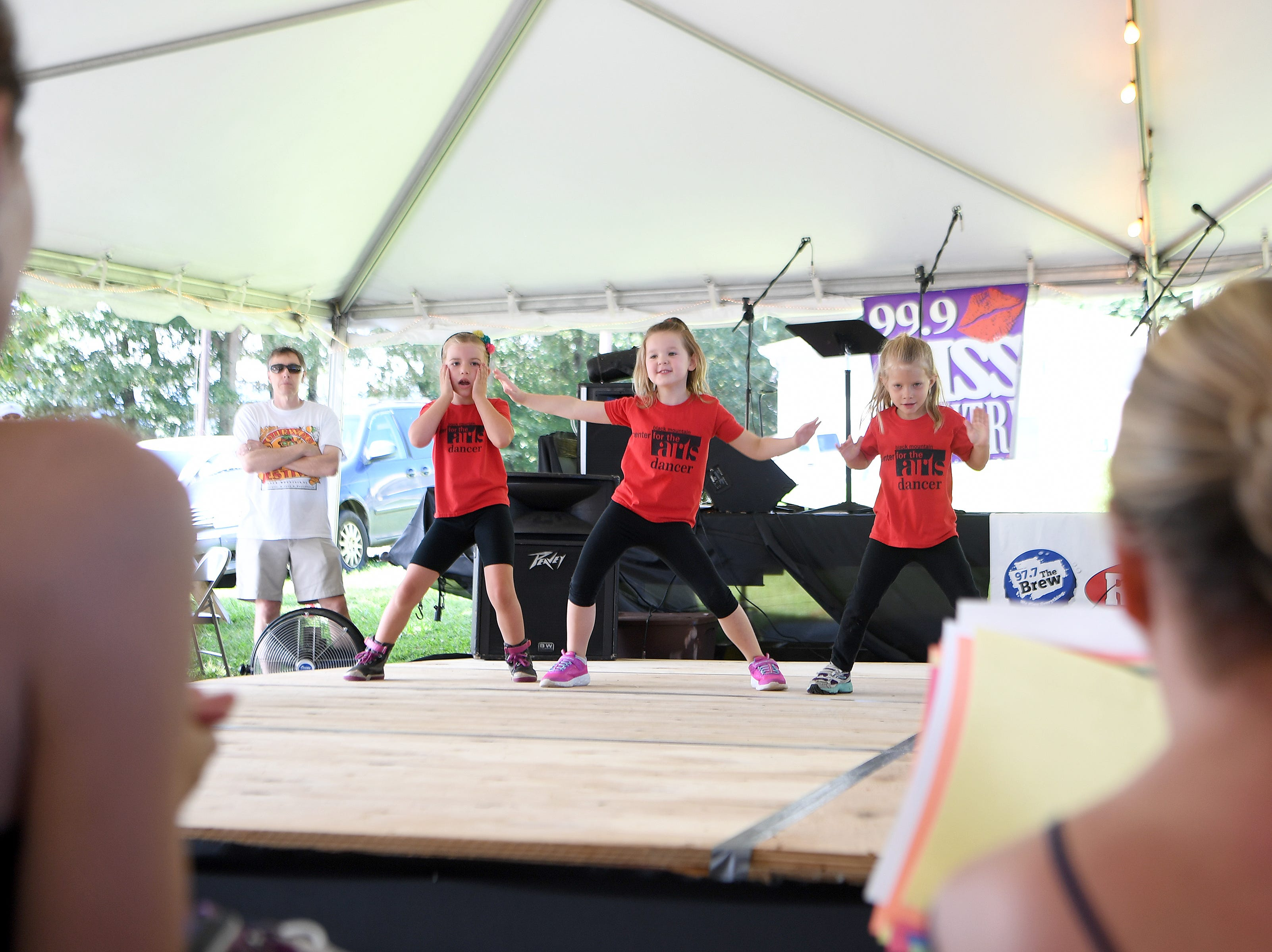 Young dancers from the Black Mountain Center for the Arts, Ember Boyd, 5, left, Vivian Pickett, 5, center, and Adelaide Christopher, 4, are directed by Amy Maze as they perform during the 41st annual Sourwood Festival in Black Mountain on Saturday, Aug. 11, 2018.