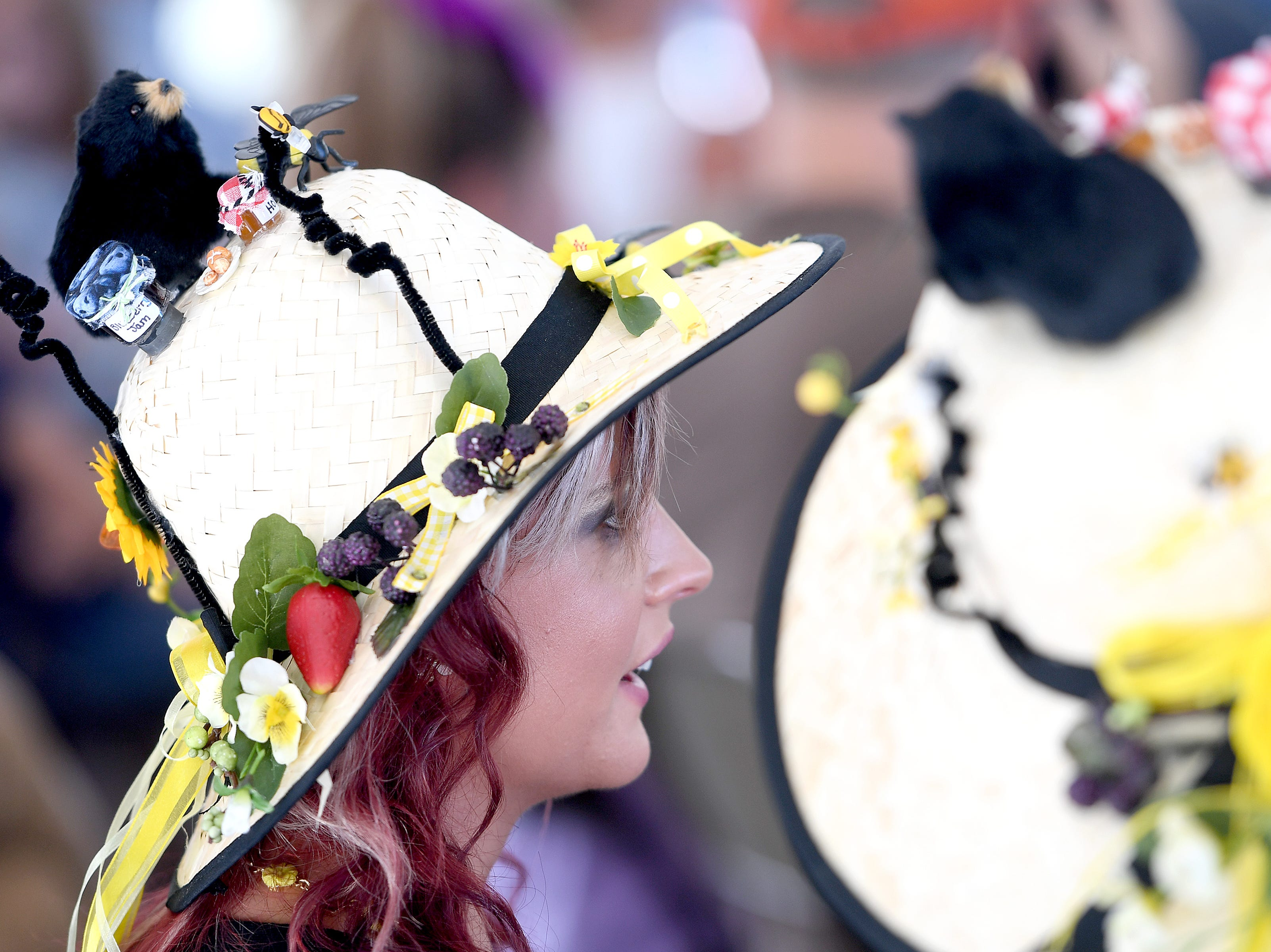 Linnea Puntigan, and her mother Laurlene Upton, both of Spartanburg, watch performances during the 41st annual Sourwood Festival in Black Mountain on Saturday, Aug. 11, 2018. Upton made their sourwood-inspired hats specifically for the festival to bring a smile to strangers' faces.
