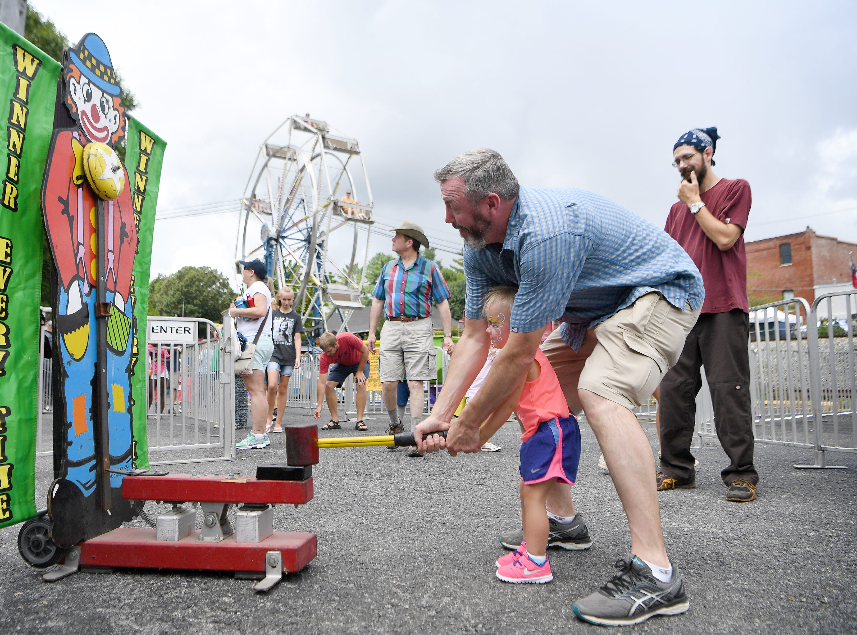 Michael Irwin helps his daughter, Josephine, 2, ring the bell on a carnival game during the 41st annual Sourwood Festival in Black Mountain on Saturday, Aug. 11, 2018.