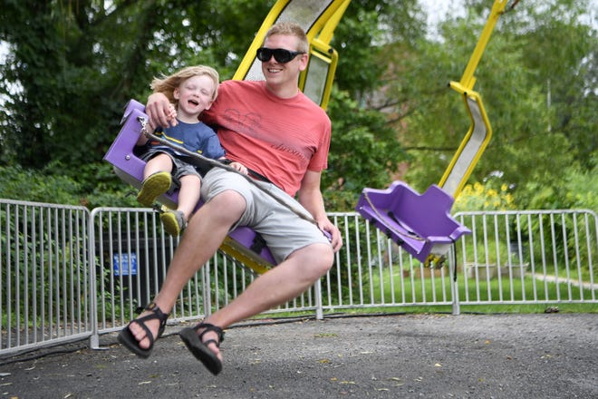 Alexander Artrip, 3, and his dad, Cory, fly through the air on a swings ride during the 41st annual Sourwood Festival, held last year in Black Mountain.
