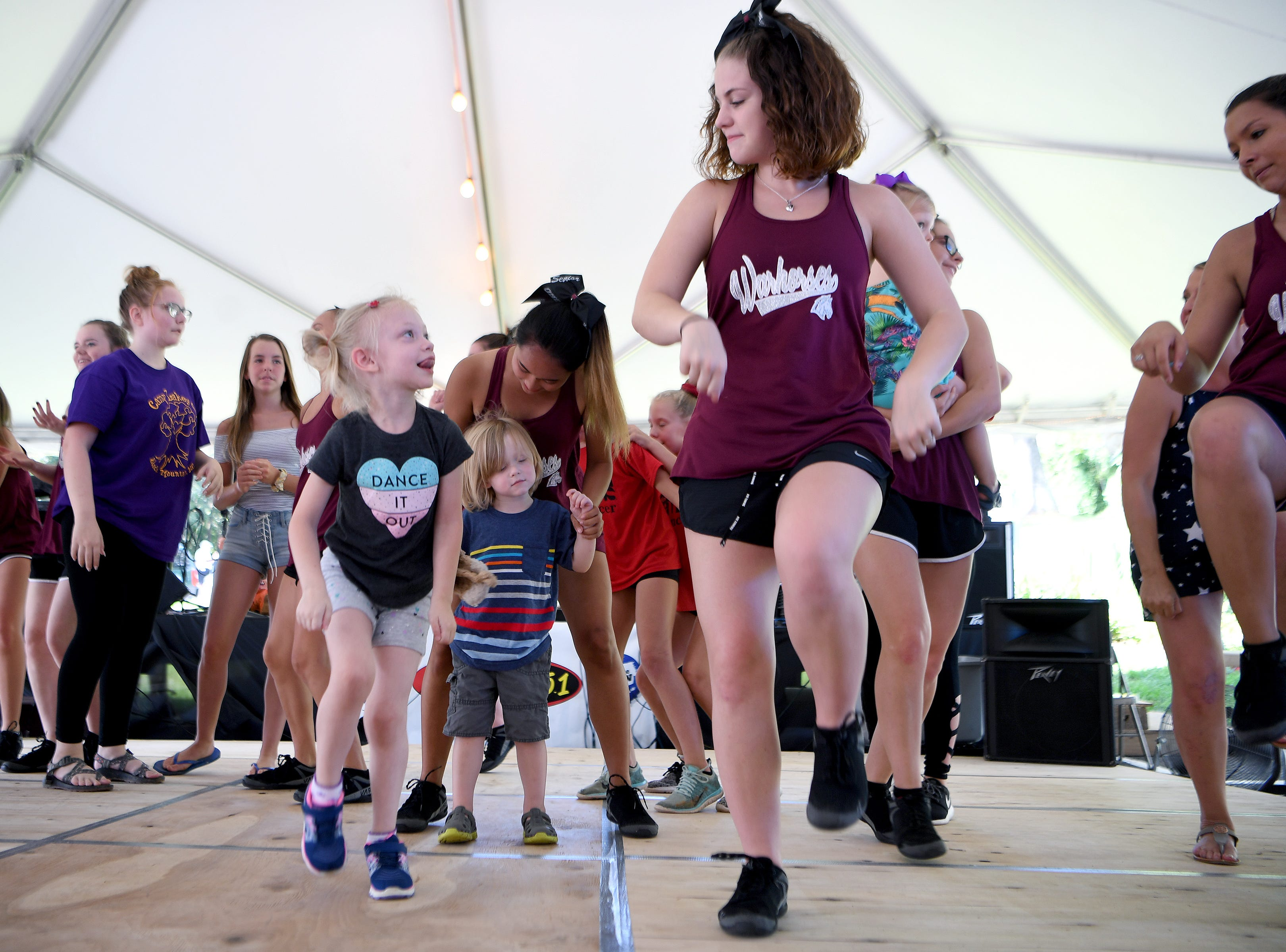 Lily Shelton, 4, looks up to Owen High School senior dance team member, Haley Roberts, 17, as children join the dancers onstage for a fun dance party number following their performances during the 41st annual Sourwood Festival in Black Mountain on Saturday, Aug. 11, 2018.