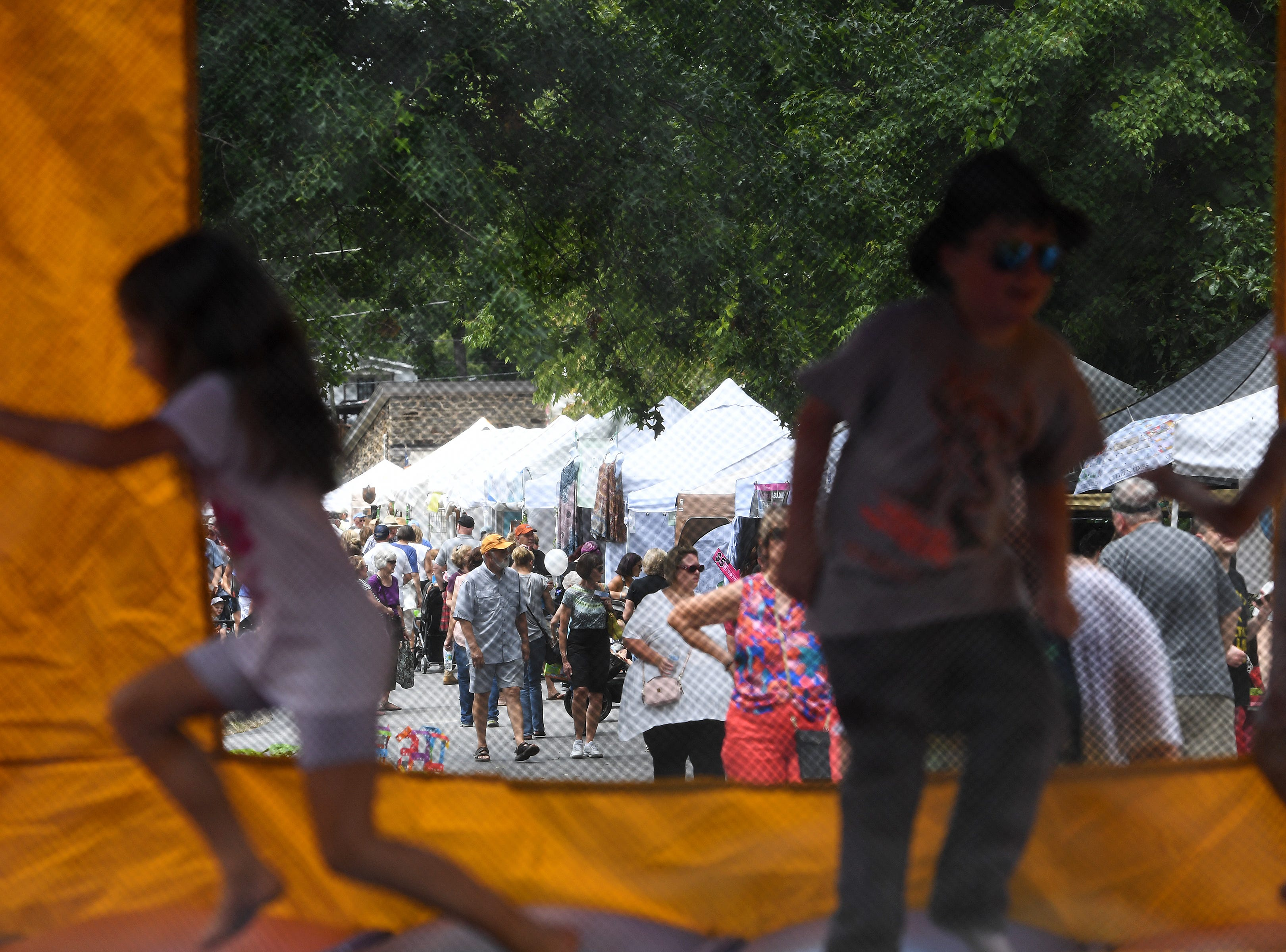 Children play in a bounce house as festival-goers shop various tents during the 41st annual Sourwood Festival in Black Mountain on Saturday, Aug. 11, 2018.