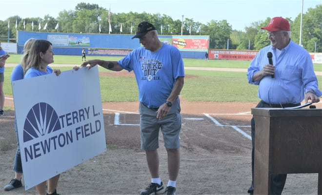 Duska Brumm, left, of the Battle Creek Parks Department, and Battle Creek Mayor Mark Behnke, right, show the new sign that will be on the field honoring Terry Newton.