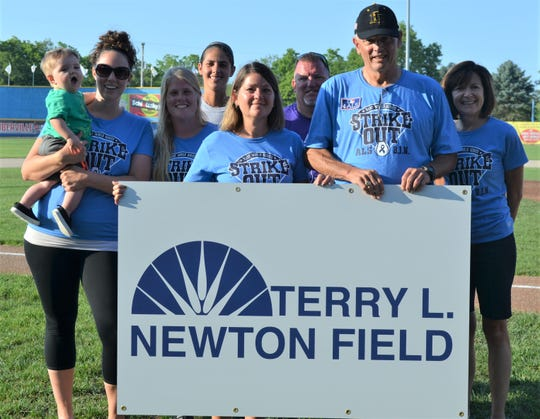 Duska Brumm of the Battle Creek Parks Department and members of the  parks department show off the new sign that will be on the field honoring Terry Newton.