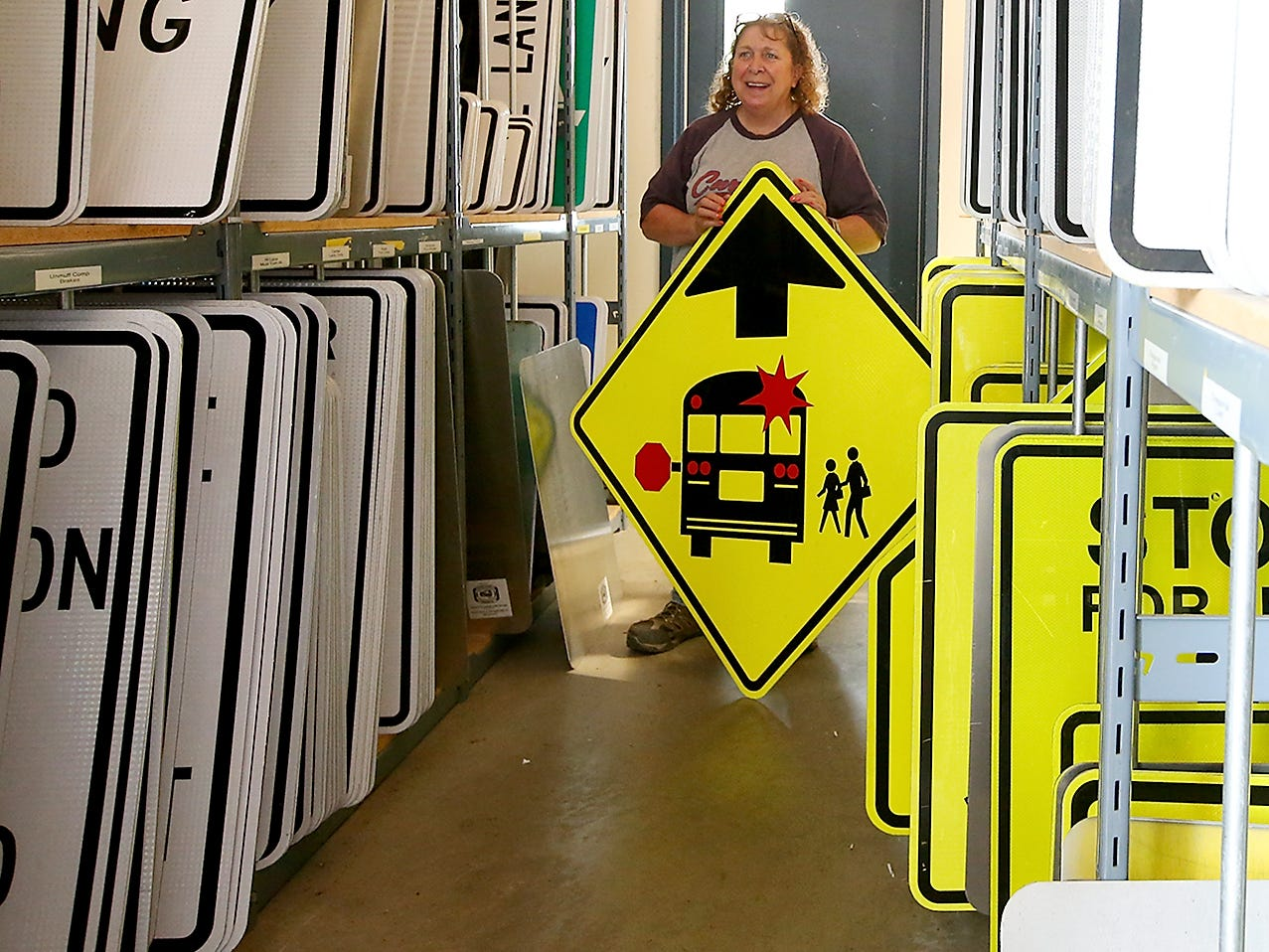 Kitsap County street sign fabricator Lynn McLean shows off one of the many signs that fill the shelves at the Kitsap County Public Works Annex on Thursday, August 2, 2018.