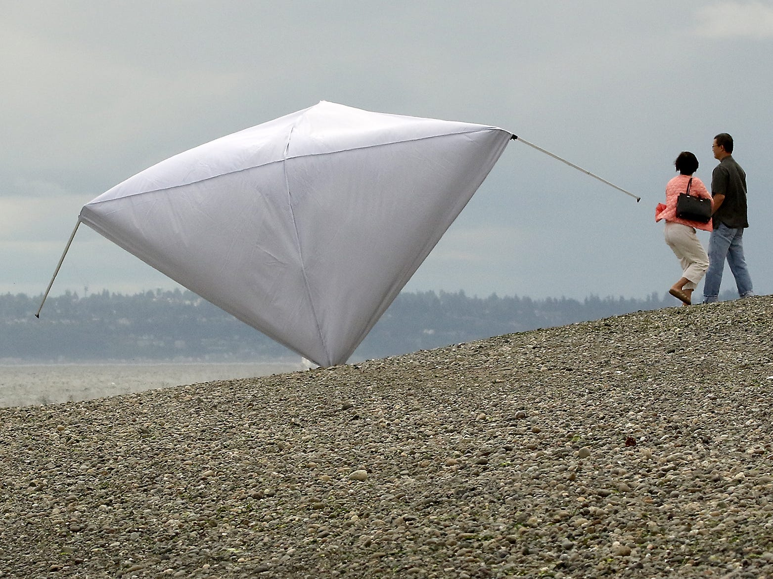 A pair of beach walkers move out of the way as a large tent tumbles down the beach after a gust of wind picked it up at Bainbridge Island's Fay Bainbridge Park on Saturday, August 11, 2018.
