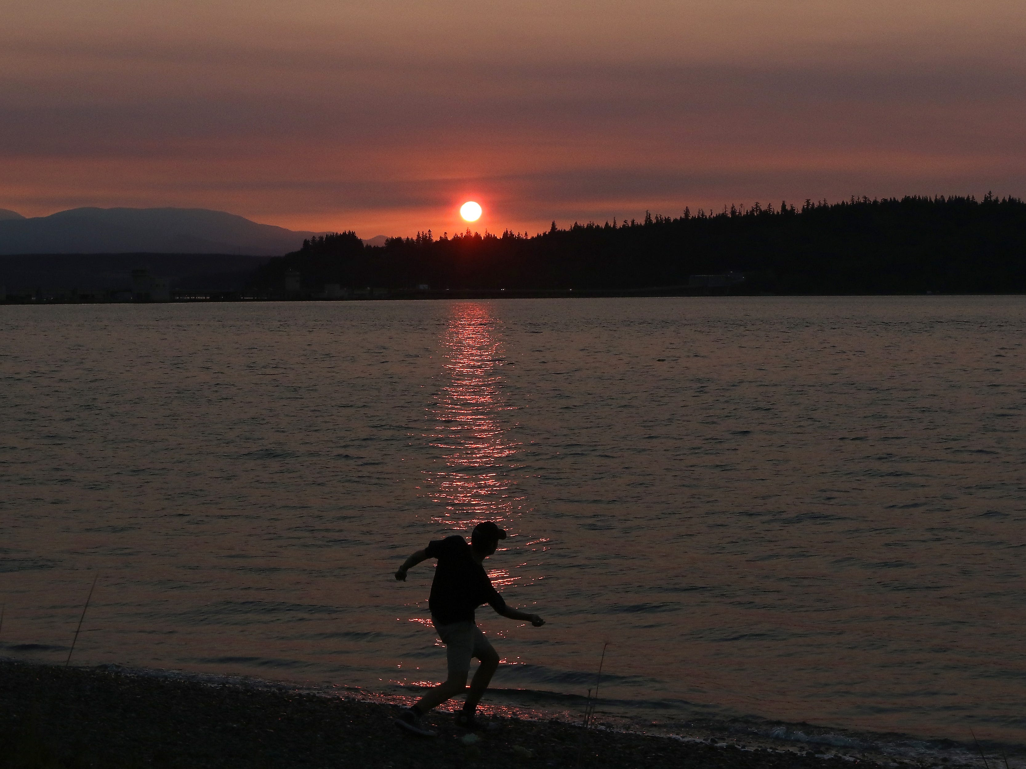 Yakov Chernick, of Indianola, skips rocks as the sun sets through the smokey haze at Salsbury Point County Park near Port Gamble on Thursday, August 9, 2018.