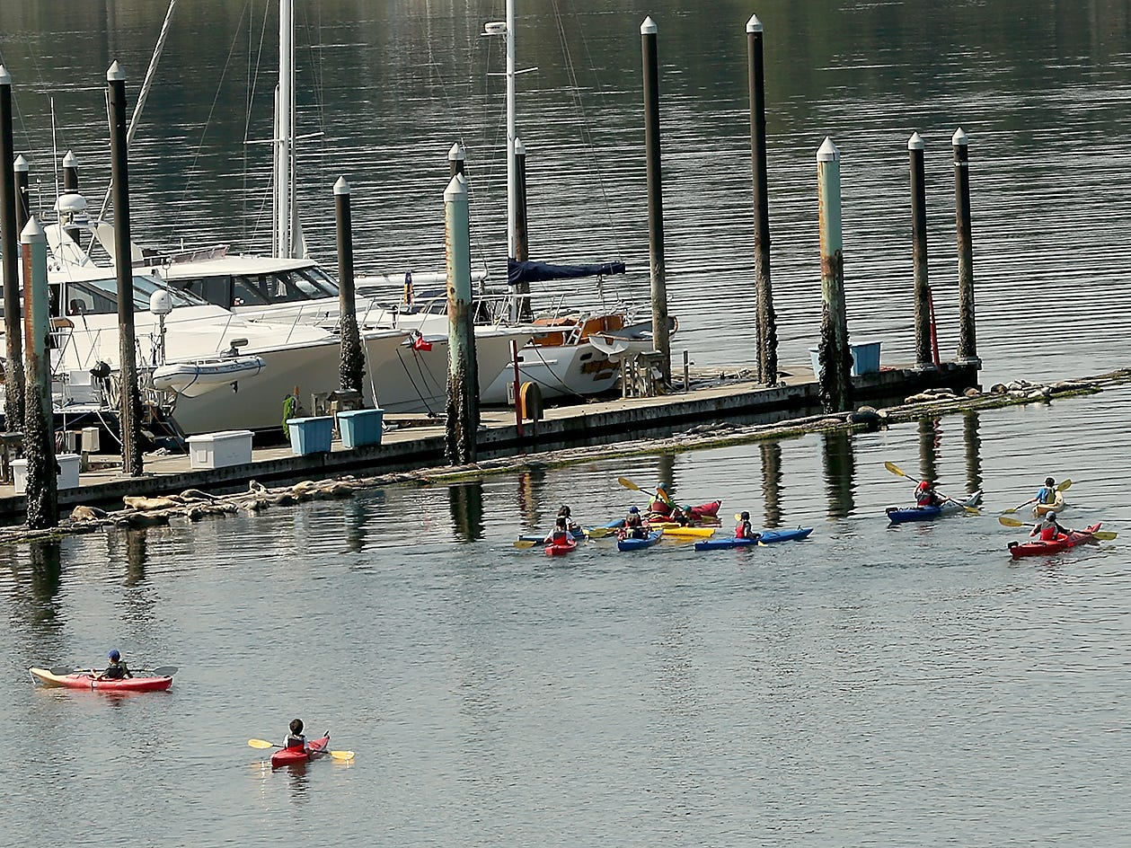Participants in a kayak summer camp paddle past the Poulsbo Yacht Club on a sunny Wednesday, August 8, 2018.