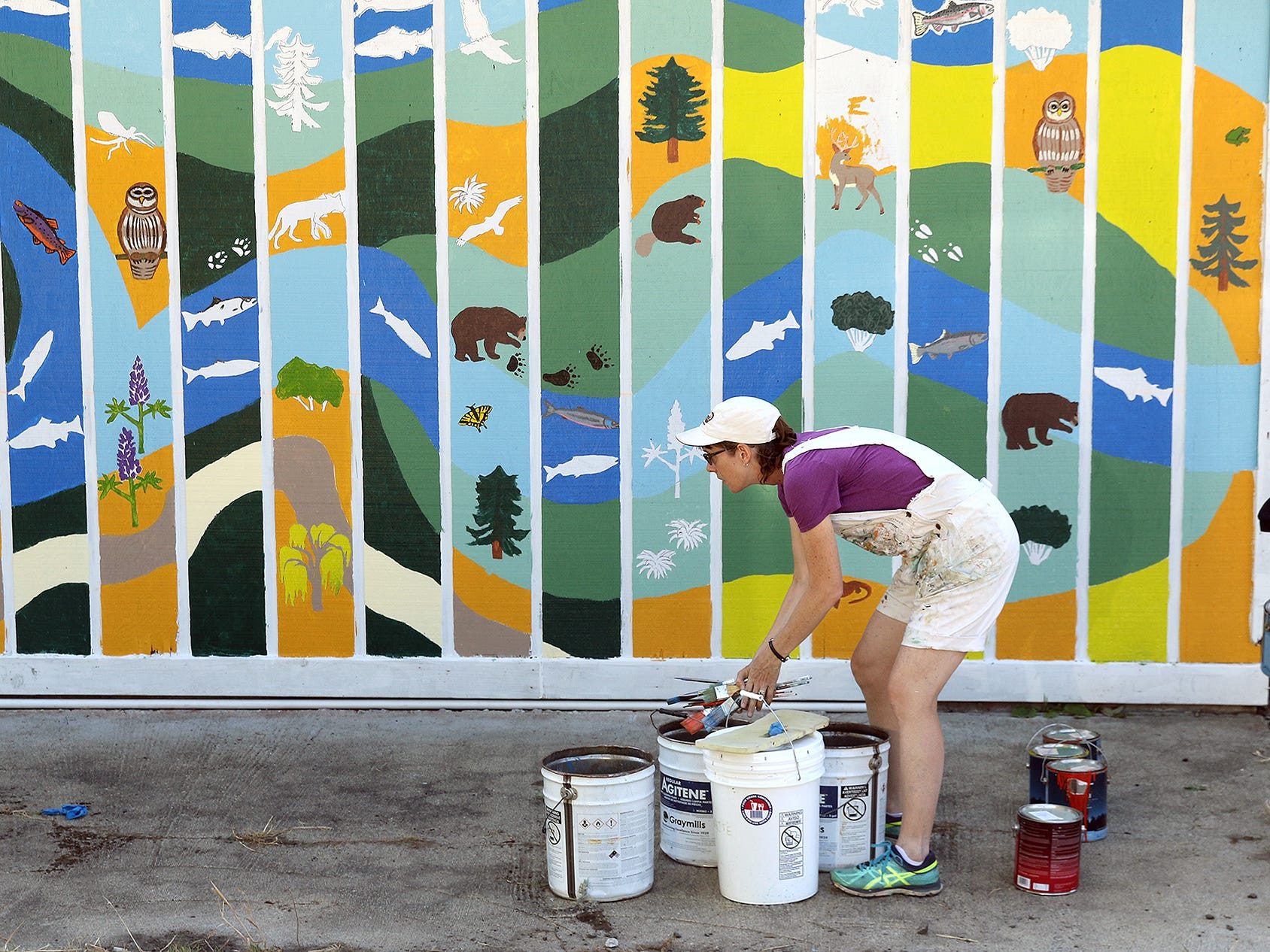 Artist Erica Applewhite, of Bremerton, takes care of the used paint brushes after the mural painting at the Pavilion building on the Markwick Property along Clear Creek in Silverdale on Wednesday August 1, 2018.