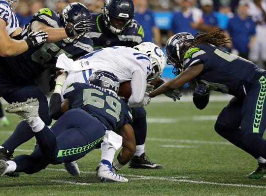 Indianapolis Colts quarterback Phillip Walker, center, is tackled by Seattle Seahawks linebacker Shaquem Griffin, right, and defensive end Jake Martin during the second half of a preseason game Thursday in Seattle.