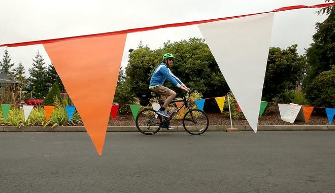 A cyclist is framed by flags of the starting area as they begin the Reform Ride for Refugees at Silverdale Lutheran Church on Saturday, August 11, 2018. Five Kitsap County churches hosted the bike ride as a fundraiser for Lutheran Community Services Northwest's refugee resettlement program.