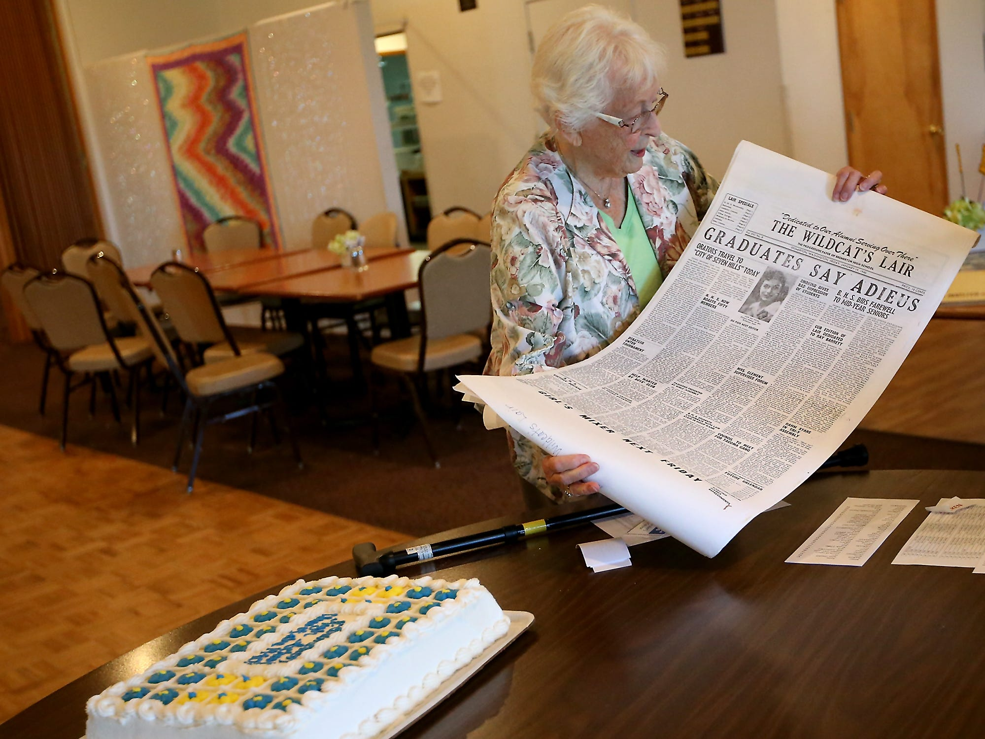 Thelma (Fuller) Gurske-Taylor, class of 1946, unrolls a copy of their school newspaper The Wildcat's Lair that she had made to display as Bremerton High School graduates from 1938 to 1948 take part in a reunion at the Elks Lodge in Bremerton on Tuesday, August 7, 2018.