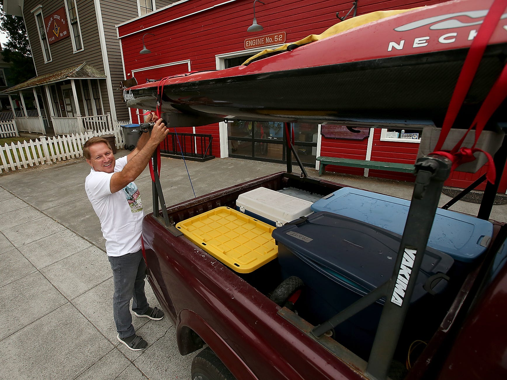 John Kuntz, owner of Olympic Outdoor Center, checks the tie down of one of his kayaks atop of his truck one last time before heading out from Port Gamble to the Columbia River, on Wednesday, August 1, 2018. Kuntz's Eri's Adventure will take him 1,250 miles from the source of the Columbia River to the Pacific Ocean.