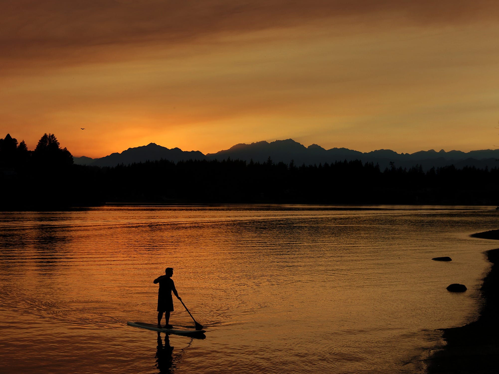 Jeremy Stitt brings his stand up paddle board in as the sun sets at the Lions Park Boat Ramp on Monday. The smoke from wildfires has made the sky a brownish orange.