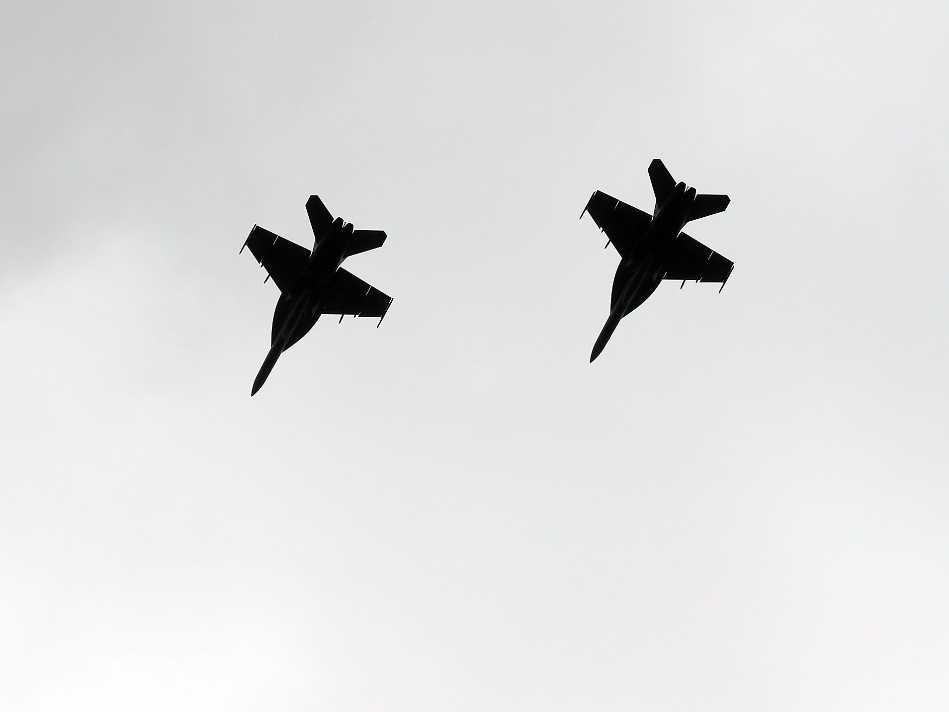 Two military fighter jets are silhouetted against the clouds as they fly over Bainbridge Island's Fay Bainbridge Park on Saturday, August 11, 2018.