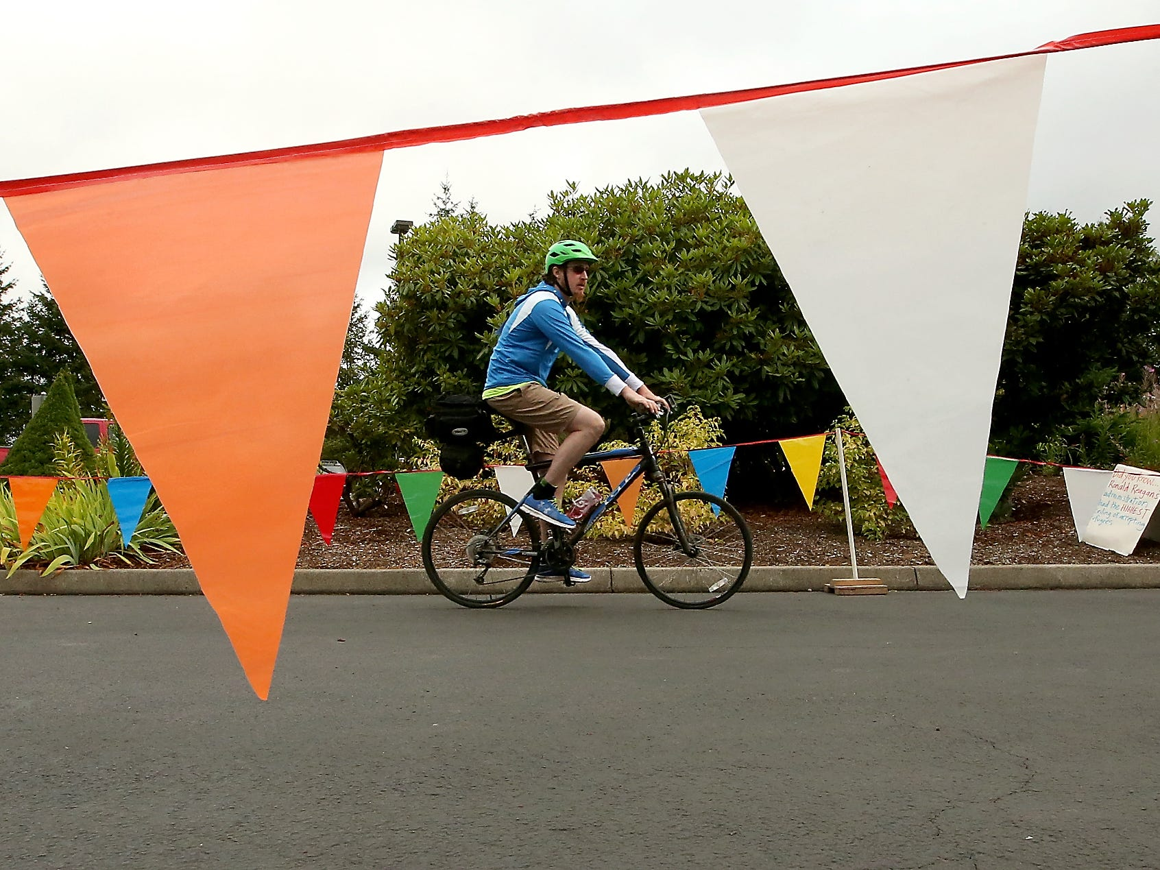 A cyclist is framed by flags of the starting area as they begin the Reform for Refugees Ride at Silverdale Lutheran Church on Saturday, August 11, 2018. Five Kitsap County churches hosted the bike ride as a fundraiser for Lutheran Community Services Northwest's refugee resettlement program.