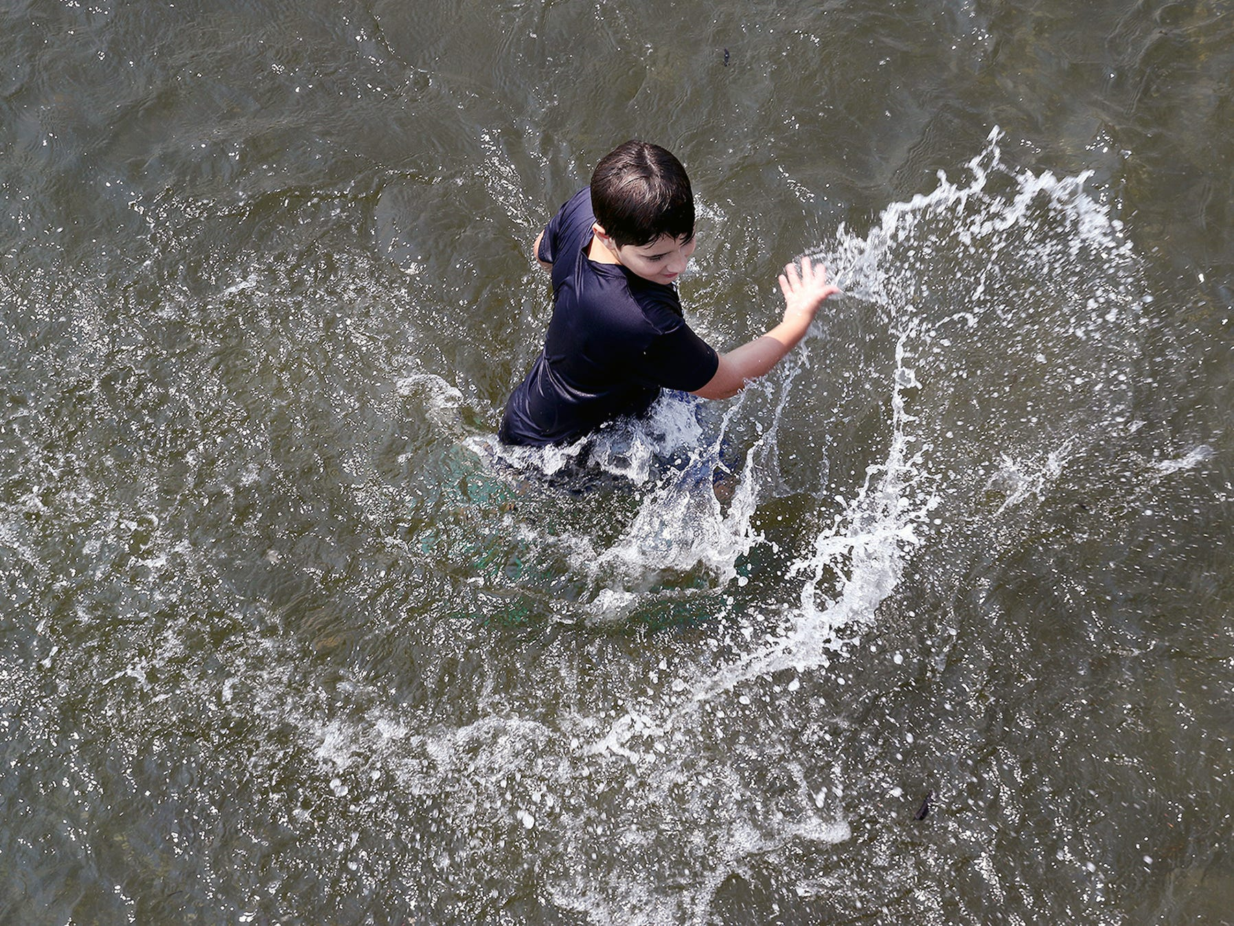 Van Kennedy, 9, splashes in the waist deep water at Silverdale Waterfront Park on a hot Monday August 6, 2018.