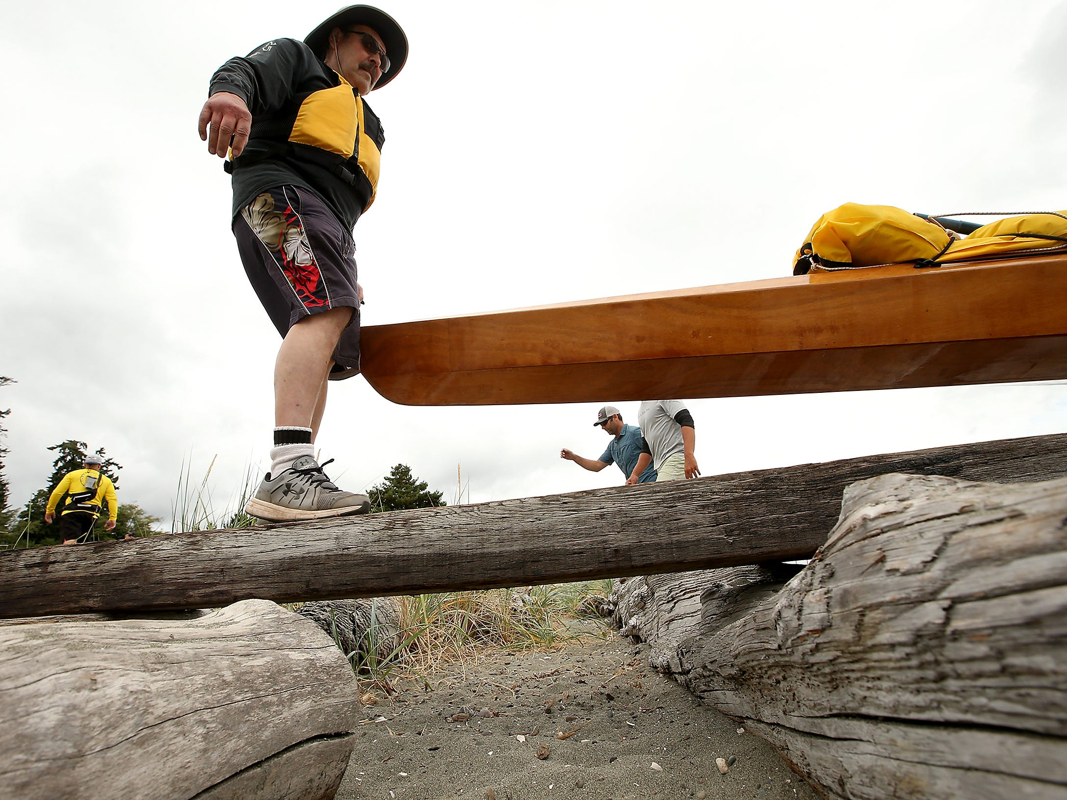 Jack Corbett, of Silverdale, carries one end of the kayak across the driftwood logs as he and fellow paddler Peter Horton carefully balance and make their way to the water for the start of Olympic Outdoor Center's Paddle Kitsap at Bainbridge Island's Fay Bainbridge Park on Saturday, August 11, 2018.