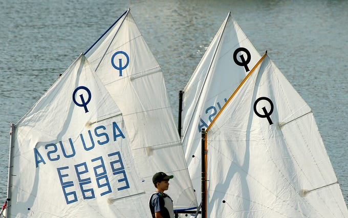 A summer sailing student makes their way among the sails as the boats prepare to launch off the shore of Bainbridge Island's Waterfront Park on Thursday, August 9, 2018.