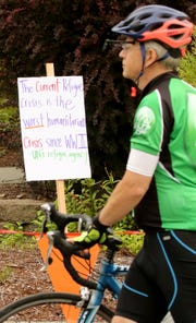 Signs about the current refugees crisis lines the starting line prior to the start of the Reform Ride for Refugees at Silverdale Lutheran Church on Saturday, August 11, 2018.