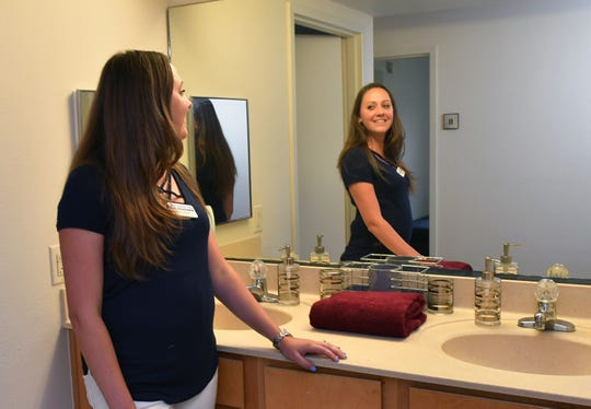 Courtney Ross, with customer service at the Melbourne Bed, Bath & Beyond, set up sample decor in a dorm room at Anderson Hall at the Florida Institute of Technology, showing examples of the kinds of accessories and furniture they offer that would be right for a dorm room.