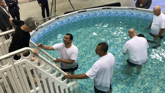 Raymona Armstrong, 77, steps into the pool to be baptized in front of 3,500 people at the Jehovah's Witness 2018 Regional Convention Saturday, Aug. 11, 2018.