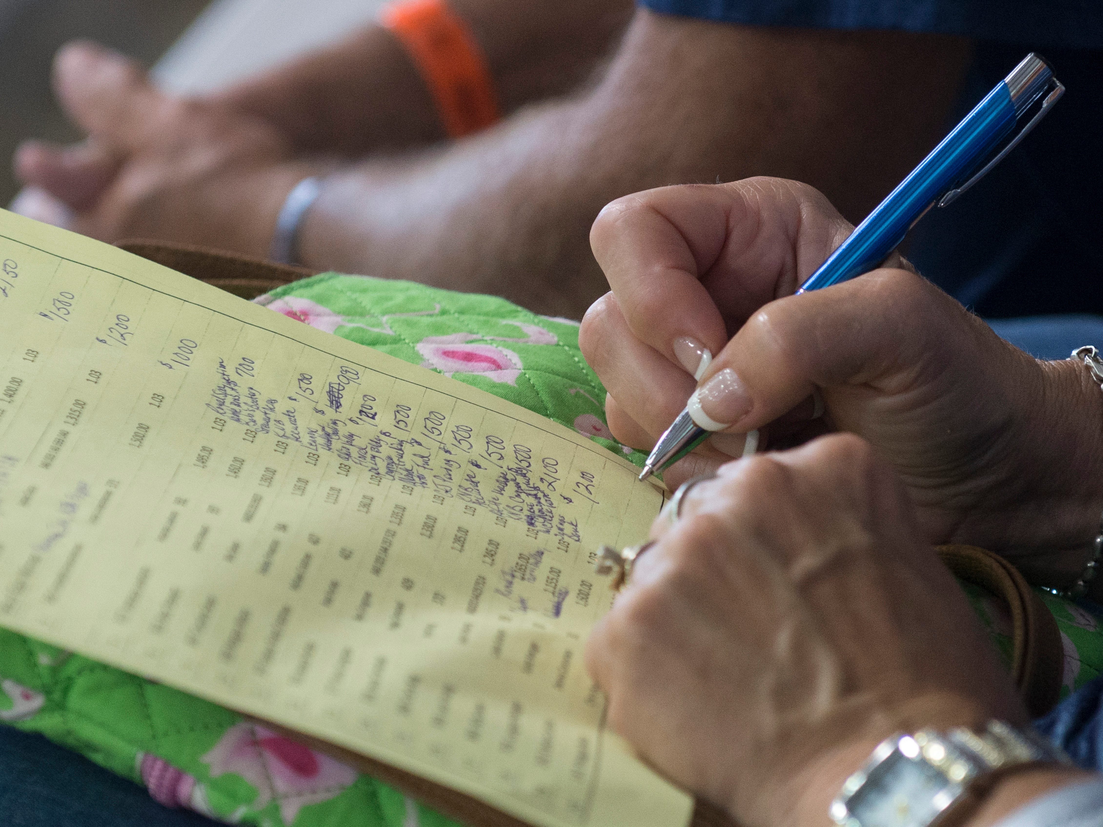 Fair attendees record bids during the Jr. Fair Market Steer, Poultry and Rabbit Sale at the Ross County Fair on August 11, 2018, in Chillicothe, Ohio.