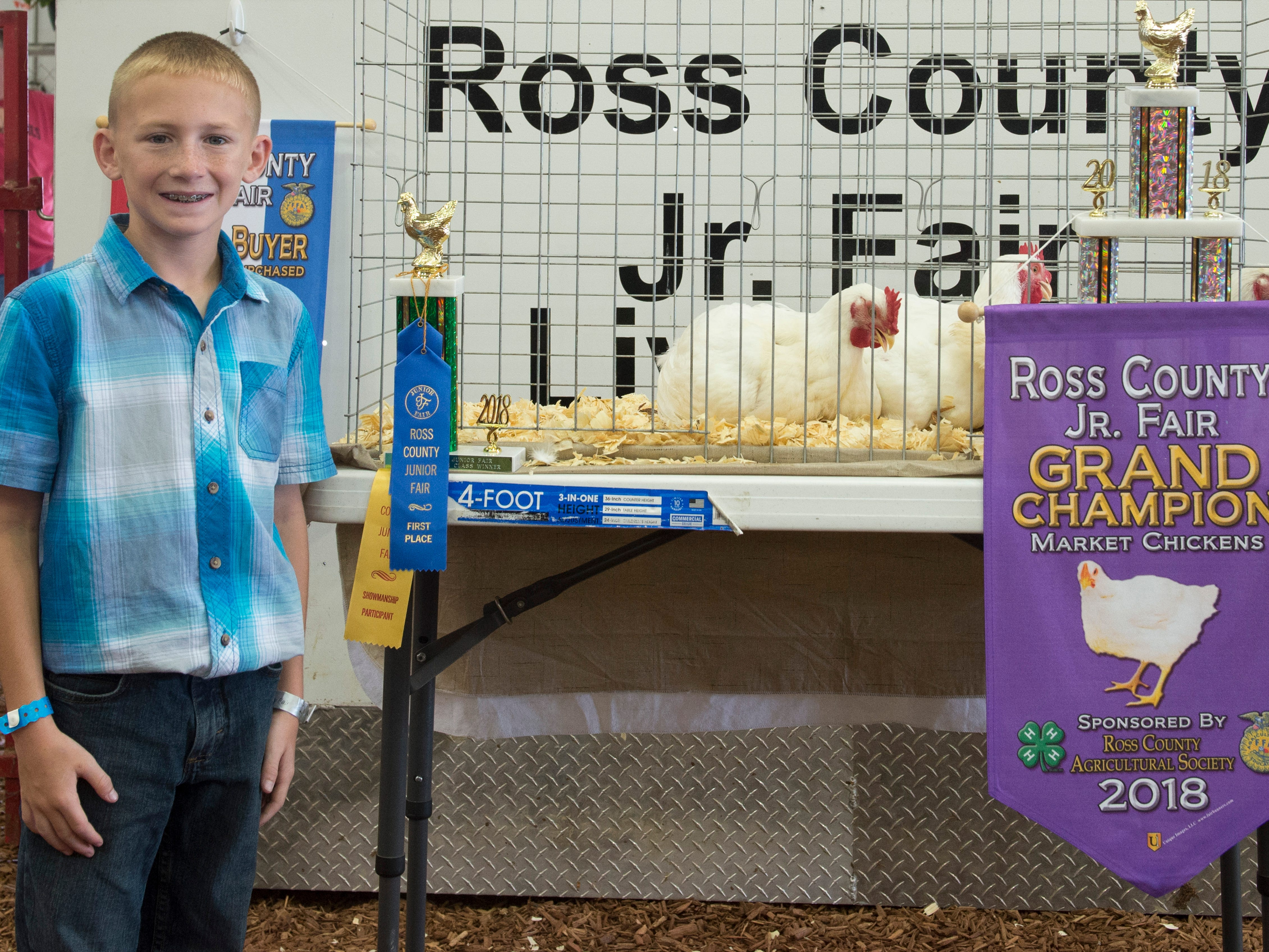 Tanner Beam poses with his Grand Champion Market Chicken during the Jr. Fair Market Steer, Poultry and Rabbit Sale at the Ross County Fair on August 11, 2018, in Chillicothe, Ohio.