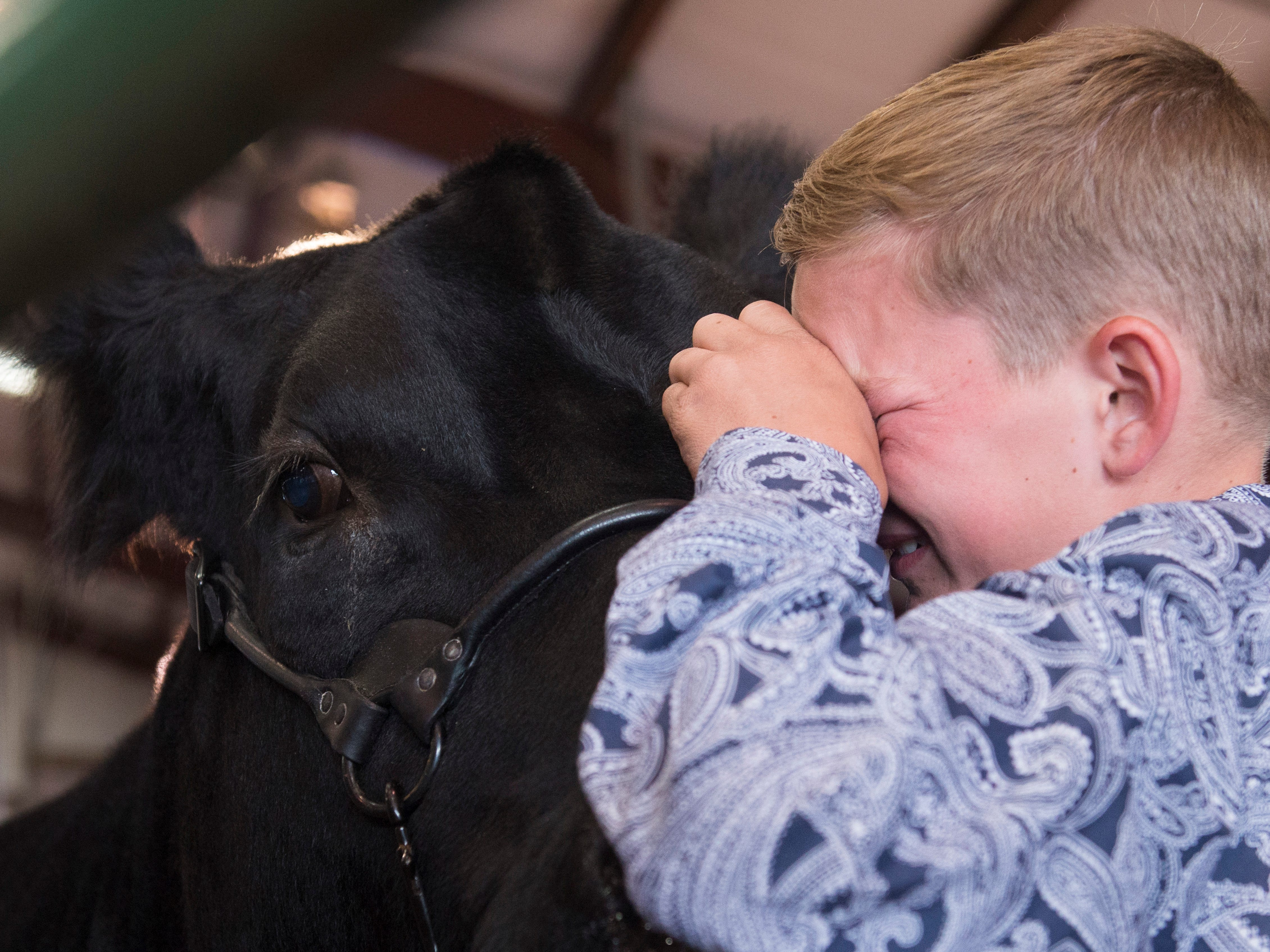 Hudson Drake says goodbye to his Grand Champion Market Steer during the Jr. Fair Market Steer, Poultry and Rabbit Sale at the Ross County Fair on August 11, 2018, in Chillicothe, Ohio.