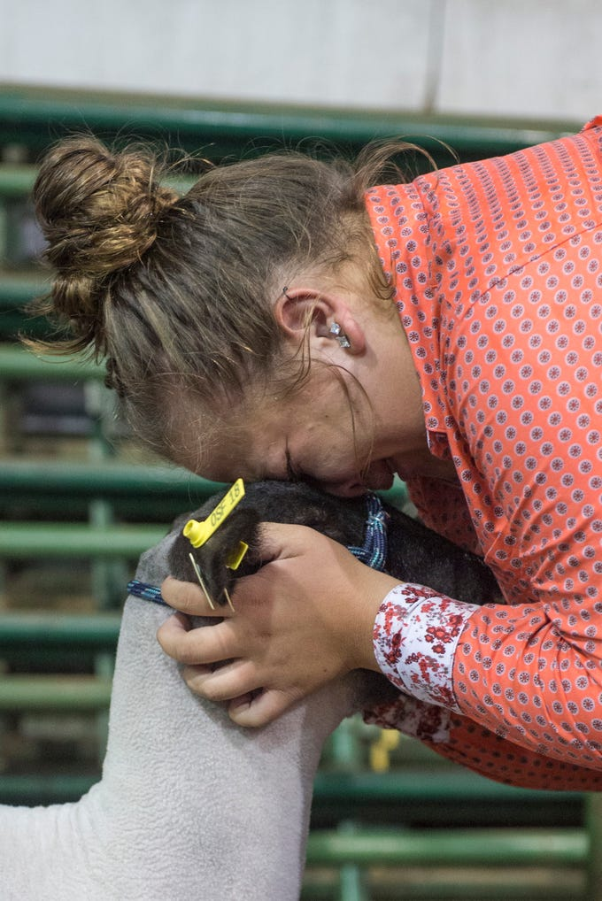 An exhibitor cries while comforting her lamb after auction at the Ross County Fair on August 10, 2018, in Chillicothe, Ohio.
