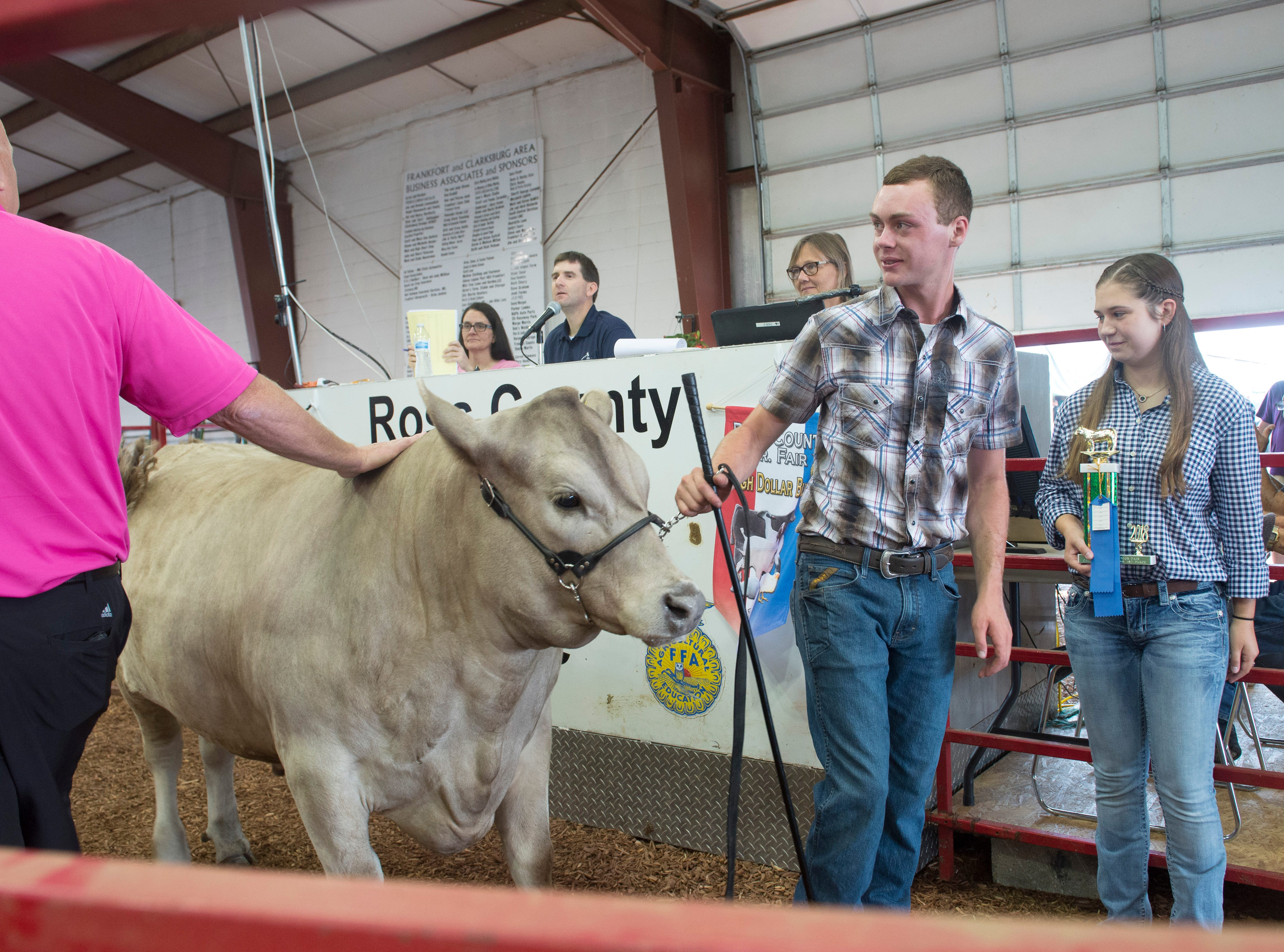 Brayden Thompson converses the buyer of his Champion Scramble Calf after auction during the Jr. Fair Market Steer, Poultry and Rabbit Sale at the Ross County Fair on August 11, 2018, in Chillicothe, Ohio.
