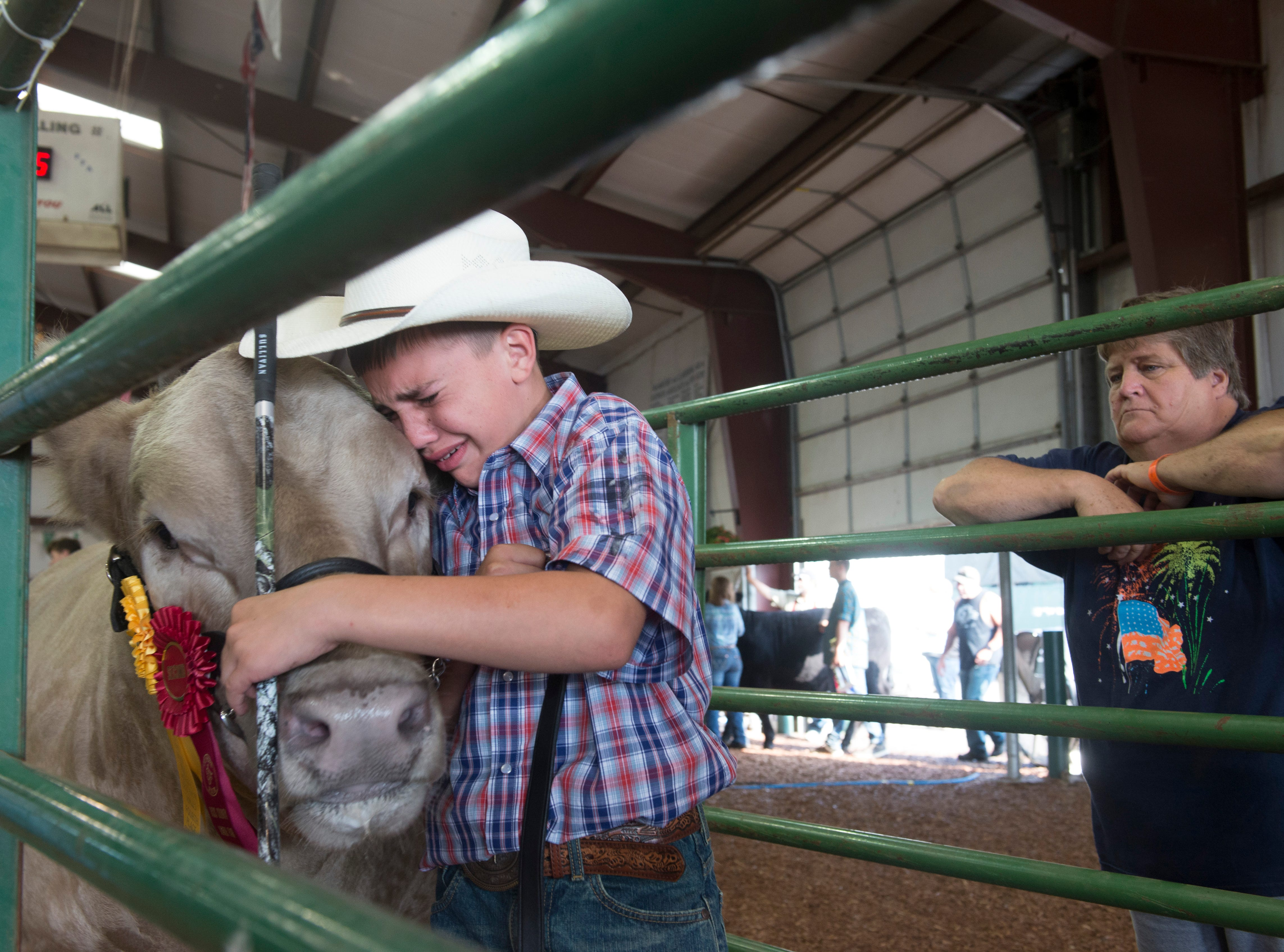 Blake Hauswirth cries while holding onto his steer after auction during the Jr. Fair Market Steer, Poultry and Rabbit Sale at the Ross County Fair on August 11, 2018, in Chillicothe, Ohio.