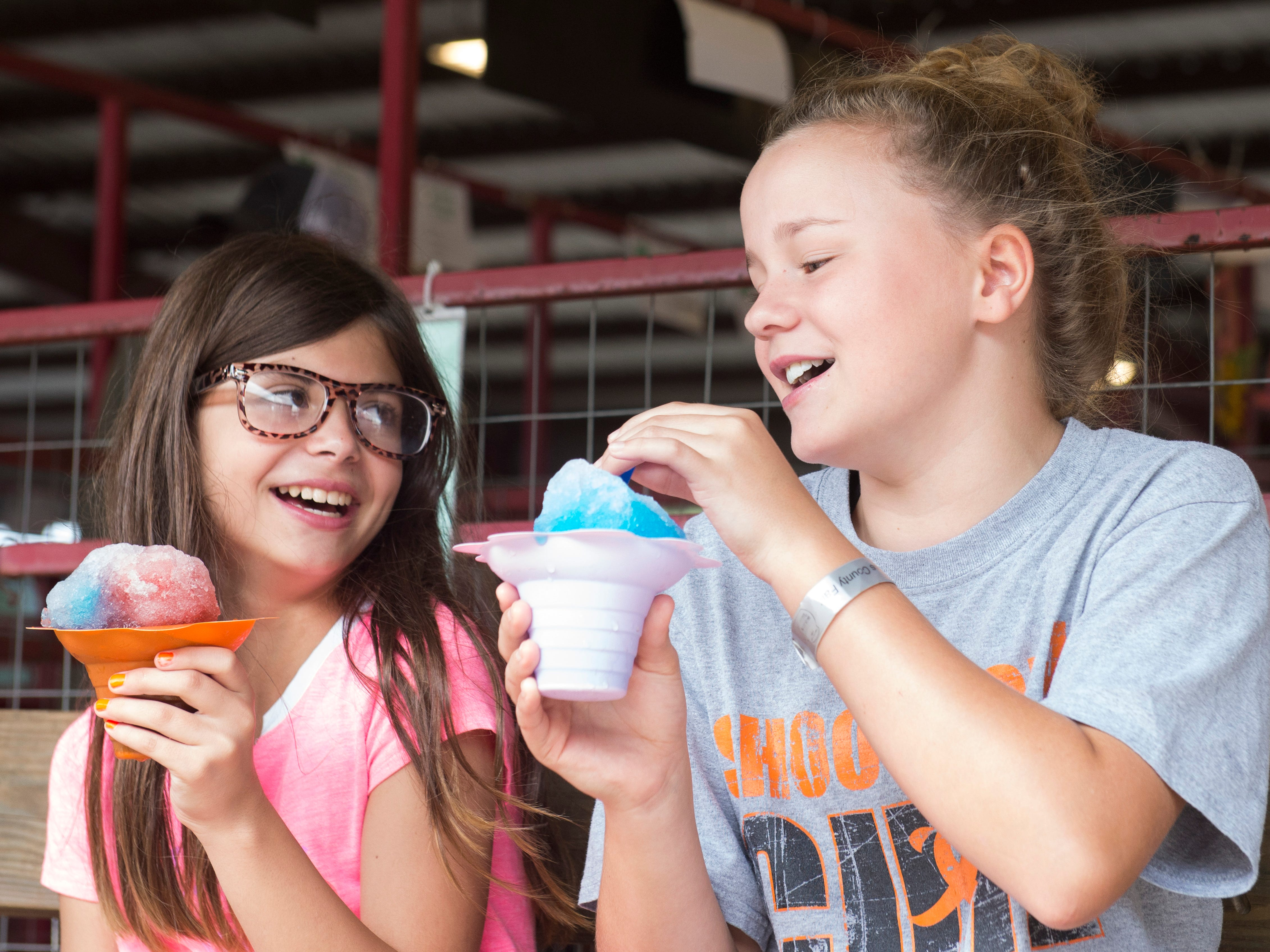 Hadley Matthews, 11, and Miranda McCloy, 11, chat over icees during the Jr. Fair Market Steer, Poultry and Rabbit Sale at the Ross County Fair on August 11, 2018, in Chillicothe, Ohio.