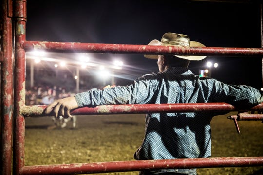 A cowboy watches the events at the Rodeo Thursday night.