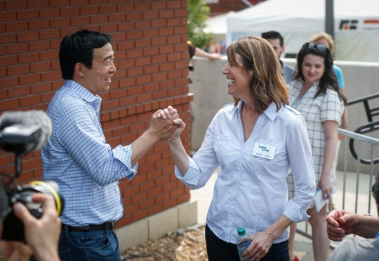 Democratic presidential hopeful Andrew Yang, left, high fives Iowa democratic congressional candidate Cindy Axne before he took the stage to speak at the Political Soapbox on Saturday, Aug. 11, 2018, during the Iowa State Fair in Des Moines.