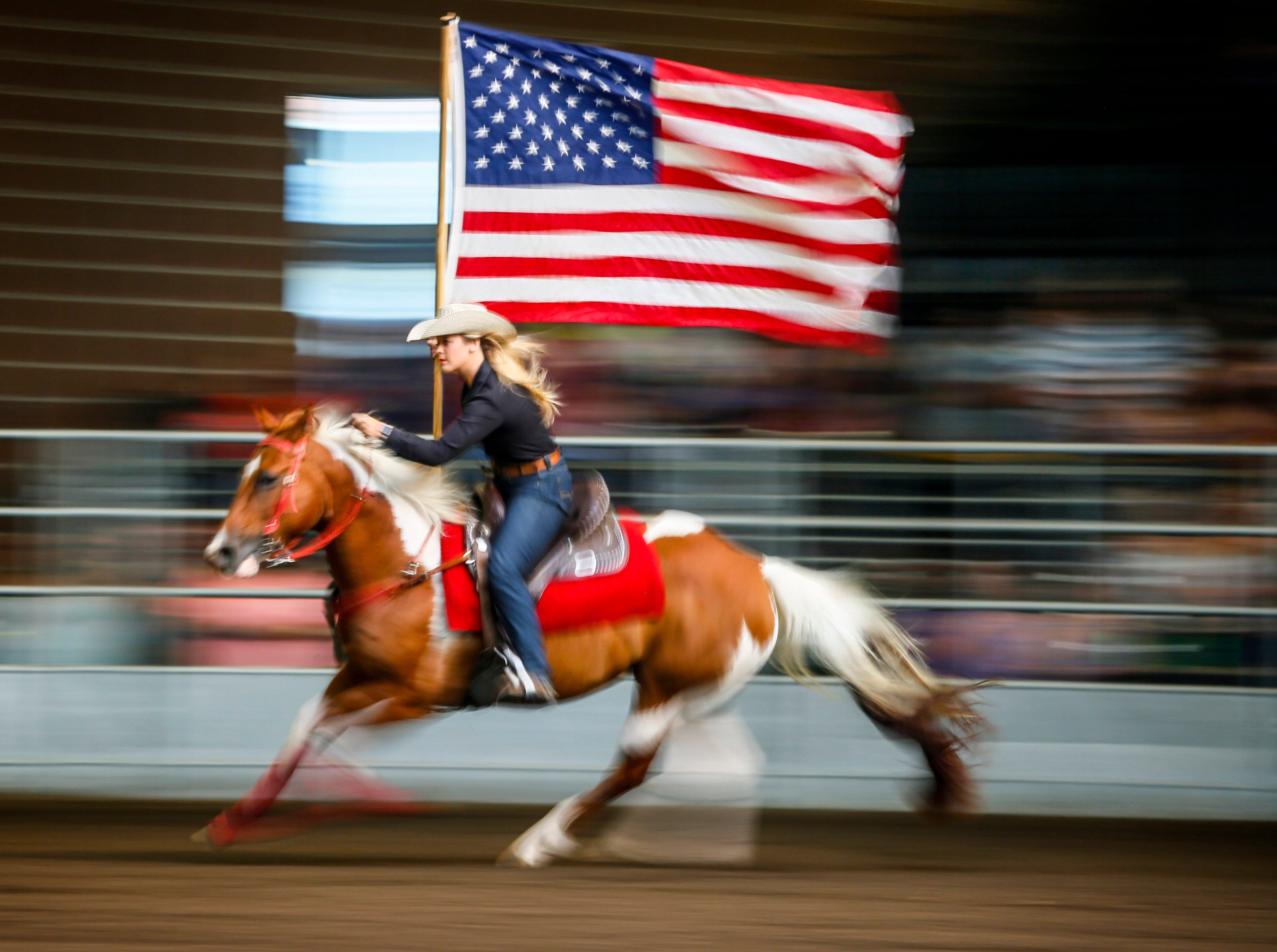 Brittany Abernathy rides with the flag during the national anthem before the Cowgirl Queen Contest at the Iowa State Fair Friday, Aug. 10, 2018.