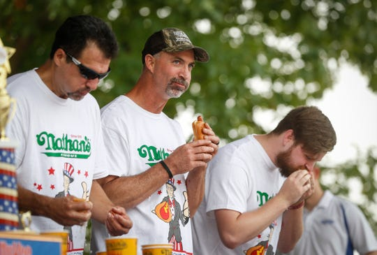 Aaron Adams of Ames, center, looks at the fans during the regional Nathan's Hot Dog eating contest on Saturday, Aug. 11, 2018, during the Iowa State Fair in Des Moines.