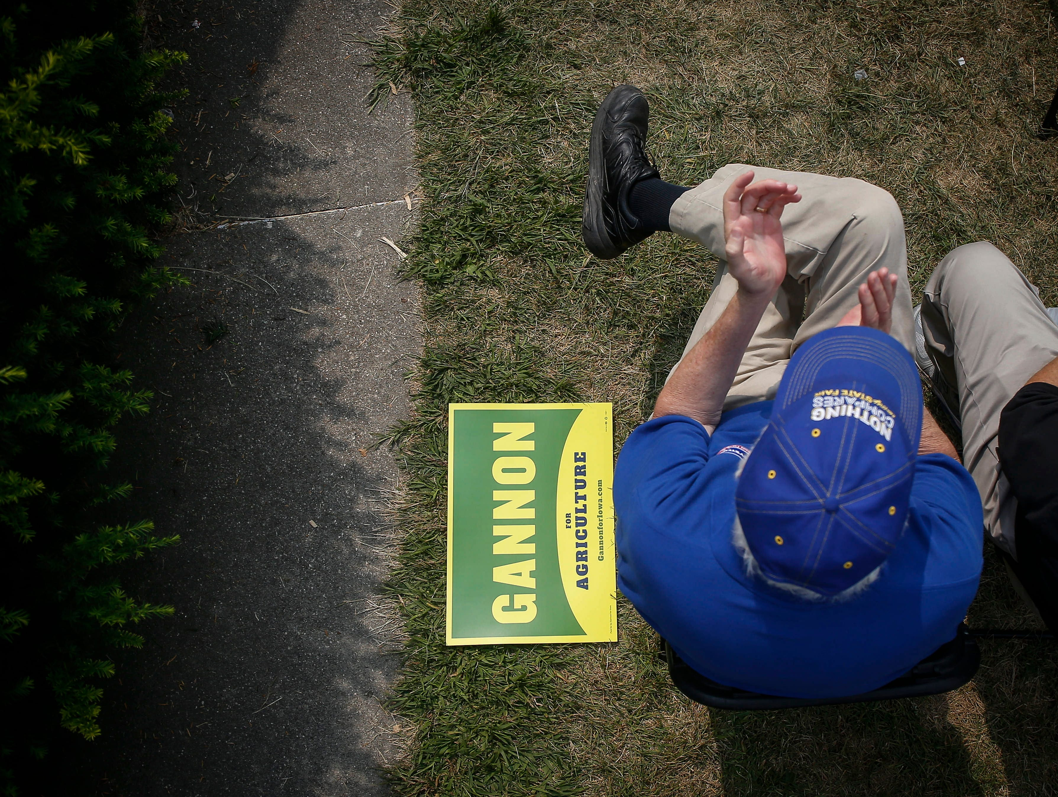 A supporter of Iowa Secretary of Agriculture candidate Tim Gannon applauds as a yard sign sits next to him during the Political Soapbox on Saturday, Aug. 11, 2018, during the Iowa State Fair in Des Moines.
