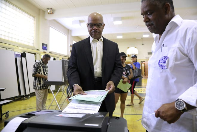 Greg Terrell, 65, lives in the historic Sherwood Forest neighborhood of Detroit and casts his vote in the Michigan primaries with assistance from Poll Worker Alvin Lee, 62, of Detroit at Pasteur Elementary on Tuesday, Aug, 7, 2018.