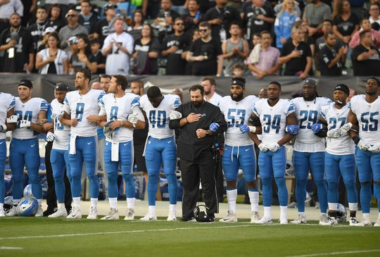 Lions coach Matt Patricia interlocks arms with his players during the national anthem before the start of the 16-10 exhibition loss to the Raiders on Friday, Aug. 10, 2018, in Oakland, Calif.