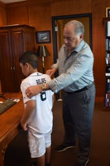 Eric Rojas, 8 years old, gets a personalized jersey from Detroit Tigers' general manager Al Avila.